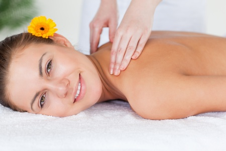 Close up of a beautiful woman having a shoulder massage in a spa photo