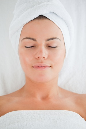 Portrait of a cute woman wearing a towel closing her eyes photo