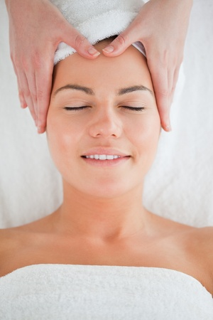 Portrait of a happy woman enjoying a facial massage in a spa photo