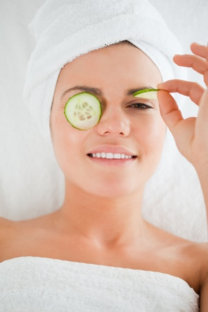 Young woman with cucumber slices on the face in a spa photo
