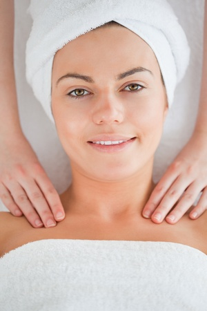 Young woman having a shoulder massage in a spa photo