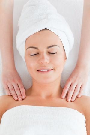 Happy woman enjoying a shoulder massage against a white background photo