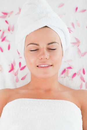 Beautiful brunette surrounded by petals in a spa photo