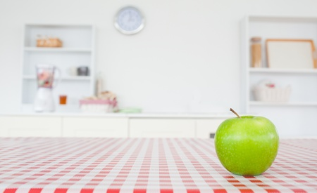 An apple on a tablecloth in a kitchen Stock Photo - 10070955