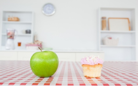 An apple and a cupcake on a tablecloth in a kitchen photo