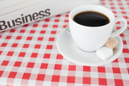 A cup of coffee and a newspaper on a tablecloth in a kitchen photo