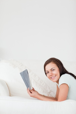 Portrait of a cute woman on a sofa holding a book looking at the camera photo