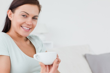 Close up of a brunette sitting on a sofa with  a cup of coffee looking at the camera photo