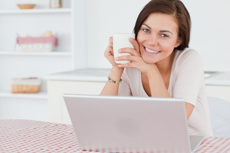 Beautiful dark-haired woman using her laptop and having a tea in her kitchen photo