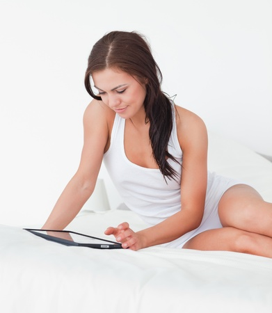 Beautiful young woman with a tablet in her bedroom photo