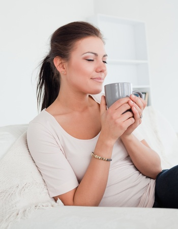 Cute brunette enjoying a cup of tea in her living room photo