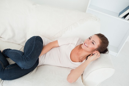 Smiling brunette calling while lying on her sofa in her living room photo