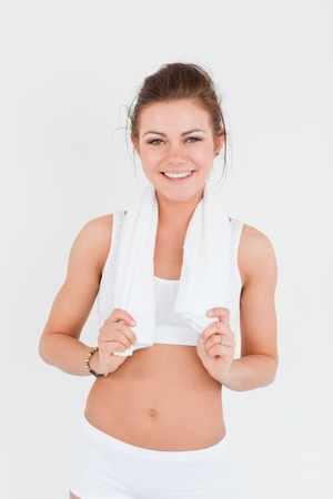Fit woman with a towel on her shoulders against a white background photo