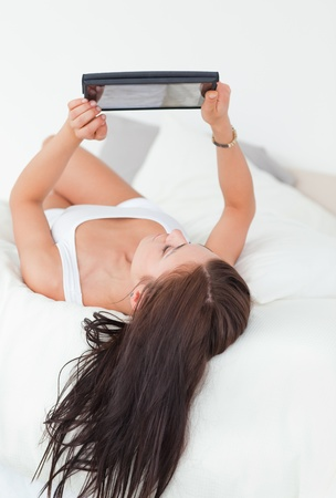 Portrait of  a beautiful woman with a tablet in her bedroom Stock Photo - 10072301