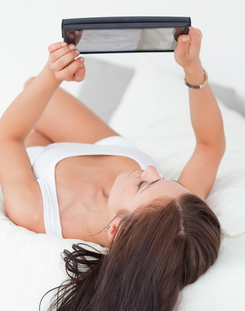Portrait of  a beautiful brunette with a tablet in her bedroom photo