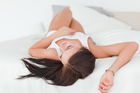 Beautiful brunette lying on her bed Stock Photo - 10071438