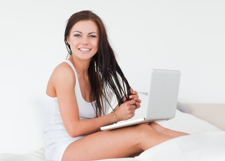 Smiling brunette with her laptop in her bedroom photo