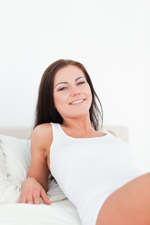 Close up of a smiling  brunette posing in her bedroom photo