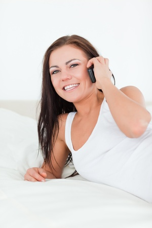 Brunette using her phone in her bedroom Stock Photo - 10070218