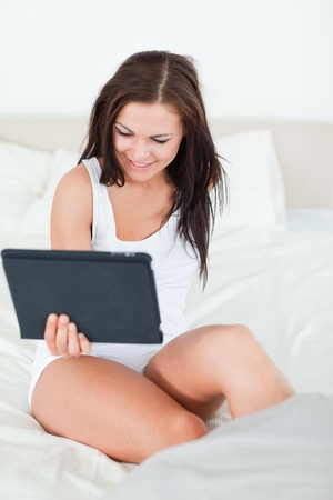 Smiling brunette with a tablet in her bedroom photo