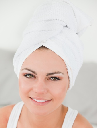 Close up of a woman with the hair wrapped into a towel against a white background photo