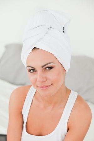 Portrait of a woman with the hair wrapped into a towel in studio photo
