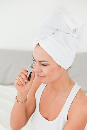 Portrait of a woman curling her eyelashes with the hair wrapped into a towel photo