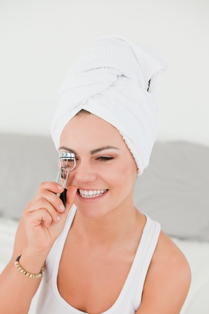Portrait of a brunette curling her eyelashes with the hair wrapped into a towel photo