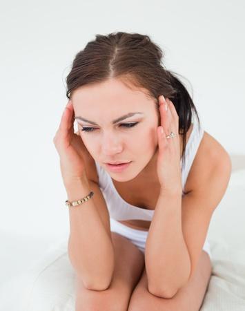 Cute brunette having a headache against a white background photo