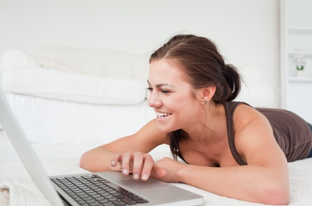 Smiling woman lying on a carpet with a laptop in her living room photo