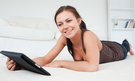 Smiling woman playing with her tablet in her living room photo