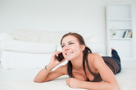 Cute young woman calling in her living room photo