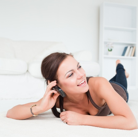 Smiling young brunette calling in her living room photo
