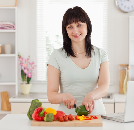 Pretty brunette woman cooking while relaxing with her laptop in the kitchen Stock Photo - 10069777