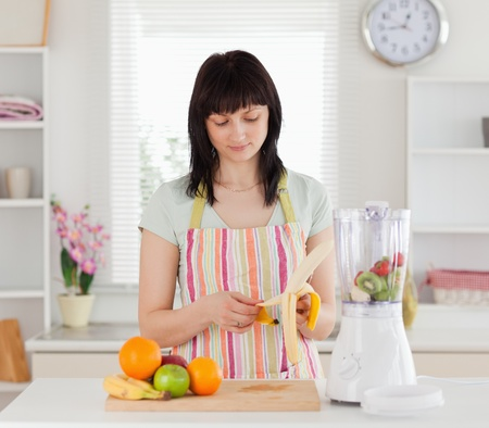 Attractive brunette woman pealing a banana while standing in the kitchen photo