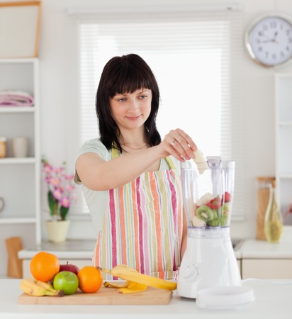 Attractive brunette woman putting vegetables in a mixer while standing in the kitchen photo