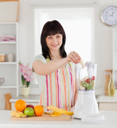 Beautiful brunette woman putting vegetables in a mixer while standing in the kitchen photo