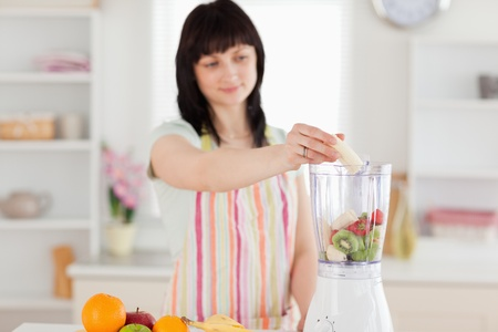 Pretty brunette woman putting vegetables in a mixer while standing in the kitchen photo