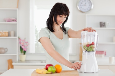 Cute brunette woman using a mixer while standing in the kitchen photo