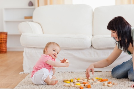 Cute woman playing with her baby in while sitting on a carpet in the living room photo