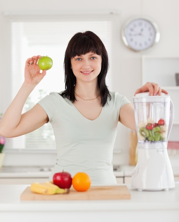 Good looking brunette female posing while standing in the kitchen photo