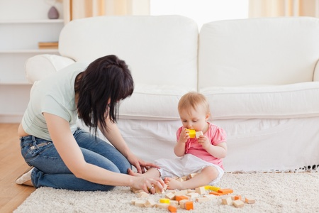wood block: Attractive woman playing with her baby in while sitting on a carpet in the living room Stock Photo