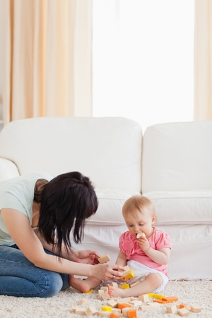 Beautiful woman playing with her baby in while sitting on a carpet in the living room photo