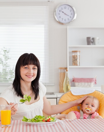 Pretty brunette woman eating a salad next to her baby while sitting in the kitchen Stock Photo - 10073022