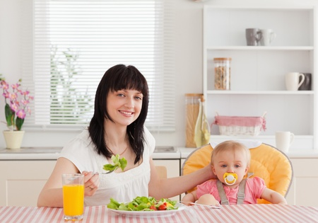 Charming brunette woman eating a salad next to her baby while sitting in the kitchen photo