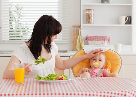Gorgeous brunette woman eating a salad next to her baby while sitting in the kitchen photo