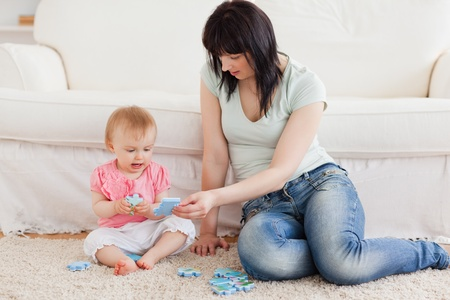 Pretty woman holding her baby in her arms while sitting on a carpet in the living room photo