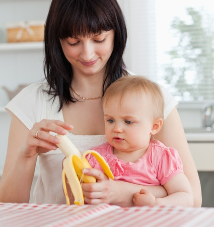 Charming brunette woman pealing a banana while holding her baby on her knees in the kitchen photo