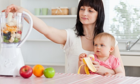 Gorgeous brunette woman putting vegetables in a mixer while holding her baby on her knees in the kitchen photo