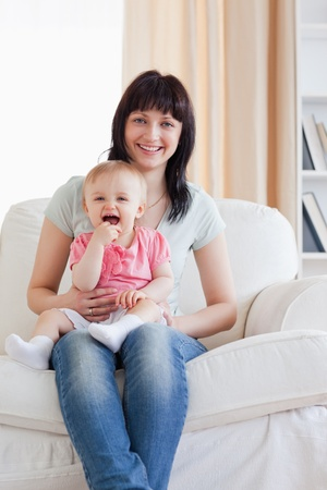Attractive woman holding her baby in her arms while sitting on a sofa in the living room photo